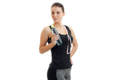 Bella ragazza di forma fisica che posa sulla macchina fotografica e che tiene una bottiglia di acqua Immagine Stock Libera da Diritti