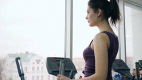 Bella ragazza di forma fisica che si esercita sul simulatore in palestra stock footage