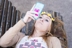 Bella ragazza di Happines con lo Smart Phone che si trova sul banco Immagini Stock Libere da Diritti