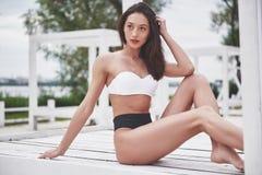 Bella ragazza di lusso esile in bikini sulla spiaggia di sabbia su un'isola tropicale Ente abbronzato sexy e figura perfetta immagini stock