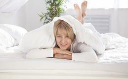Bella ragazza di mattina a letto che esamina macchina fotografica Fotografie Stock Libere da Diritti