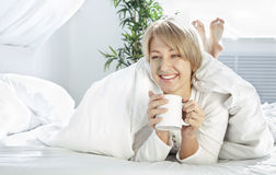 Bella ragazza di mattina a letto con la tazza Fotografie Stock Libere da Diritti