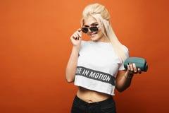 Bella, ragazza di modello bionda alla moda e sexy con l'ente perfetto in maglietta alla moda ed in jeans neri che regolano i suoi immagine stock