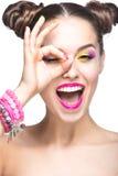 Bella ragazza di modello con trucco colorato luminoso e smalto nell'immagine di estate Fronte di bellezza Chiodi colorati short Fotografia Stock