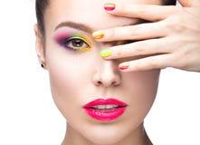 Bella ragazza di modello con trucco colorato luminoso e smalto nell'immagine di estate Fronte di bellezza Chiodi colorati short Immagine Stock