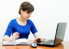 Bella ragazza di seduta in un ufficio dietro uno scrittorio Fotografia Stock
