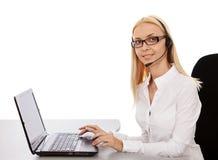 Bella ragazza di segretario in cuffie per un computer portatile, sorridenti Fotografia Stock