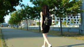 Bella ragazza di sport in un vestito nero e con uno zaino che cammina giù la via archivi video