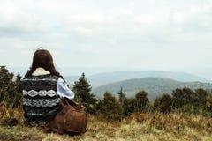 Bella ragazza di viaggio alla moda felice che si siede nelle montagne Immagini Stock