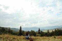 Bella ragazza di viaggio alla moda felice che si siede nelle montagne Immagine Stock Libera da Diritti
