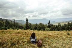 Bella ragazza di viaggio alla moda felice che si siede nelle montagne Fotografia Stock