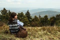 Bella ragazza di viaggio alla moda felice che si siede nelle montagne Fotografie Stock