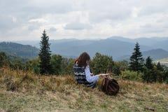 Bella ragazza di viaggio alla moda felice che si siede nelle montagne Fotografie Stock Libere da Diritti