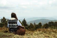 Bella ragazza di viaggio alla moda felice che si siede nelle montagne Fotografia Stock Libera da Diritti