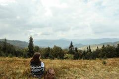 Bella ragazza di viaggio alla moda felice che si siede nelle montagne Immagine Stock