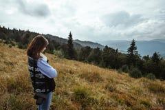 Bella ragazza di viaggio alla moda felice nelle montagne sull'sedere Fotografie Stock