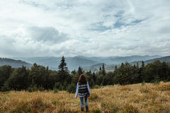 Bella ragazza di viaggio alla moda felice nelle montagne sull'sedere Fotografia Stock Libera da Diritti