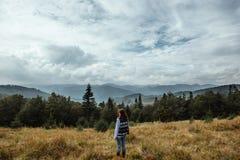 Bella ragazza di viaggio alla moda felice nelle montagne sull'sedere Fotografie Stock Libere da Diritti