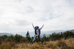 Bella ragazza di viaggio alla moda felice nelle montagne sull'sedere Immagine Stock Libera da Diritti