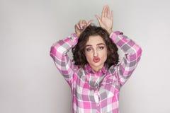 Bella ragazza divertente con la camicia a quadretti rosa, acconciatura riccia immagine stock
