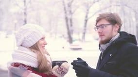 Bella ragazza ed uomo che parlano e che sorridono mentre stando con le tazze di cacao caldo in loro mani nel parco di inverno 4K archivi video