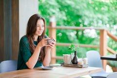 Bella ragazza elegante che mangia prima colazione al caffè all'aperto Caffè bevente della giovane donna urbana felice Fotografia Stock Libera da Diritti
