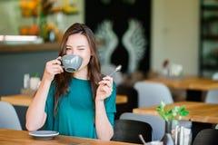 Bella ragazza elegante che mangia prima colazione al caffè all'aperto Caffè bevente della giovane donna urbana felice Fotografie Stock Libere da Diritti