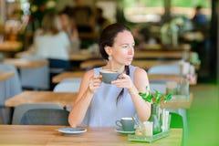 Bella ragazza elegante che mangia prima colazione al caffè all'aperto Caffè bevente della giovane donna urbana felice Immagine Stock