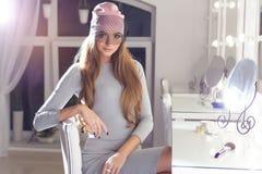 Bella ragazza elegante sexy alla moda con il cappuccio alla moda dei capelli lunghi sulla sua testa con una sera che si siede tru Immagine Stock