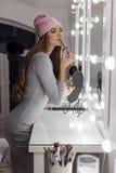 Bella ragazza elegante sexy alla moda con il cappuccio alla moda dei capelli lunghi sulla sua testa con una sera che si siede tru Fotografie Stock