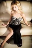 Bella ragazza elegante in una gonna stretta che posa sul sofà Trucco e acconciatura professionali fotografia stock libera da diritti