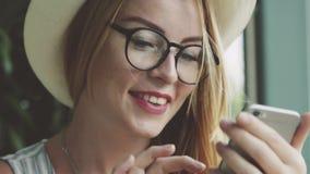 Bella ragazza emozionale che manda un sms sul telefono cellulare Grinza femminile e sorridere stock footage