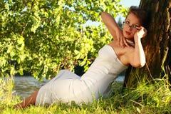 Bella ragazza emozionale in un vestito bianco che si trova sull'erba vicino Fotografia Stock