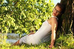 Bella ragazza emozionale in un vestito bianco che si trova sull'erba vicino Fotografie Stock Libere da Diritti