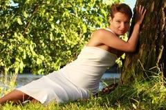 Bella ragazza emozionale in un vestito bianco che si trova sull'erba vicino Immagini Stock