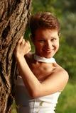 Bella ragazza emozionale in un vestito bianco che sta all'albero Fotografia Stock Libera da Diritti