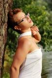 Bella ragazza emozionale in un vestito bianco che sta all'albero Fotografie Stock