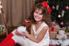 Bella ragazza emozionale In uno studio domestico per il nuovo anno ed il Natale In un vestito bianco con un arco rosso ed i calzi Immagini Stock