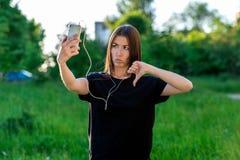 Bella ragazza europea di estate in aria aperta Mostra emozionalmente un gesto con una mano dei pollici-giù Dislajk I fa fotografie stock libere da diritti