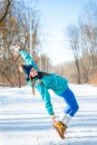 Bella ragazza felice in abiti sportivi su una parte posteriore della foresta di inverno Fotografia Stock