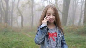 Bella ragazza felice che cammina dalla foresta e dal telefono cellulare di conversazione stock footage