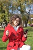 Bella ragazza felice che manda un sms sul telefono in parco Fotografia Stock