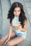 Bella ragazza felice che si siede sulle scale in parco e caffè di ghiaccio bevente Immagine Stock