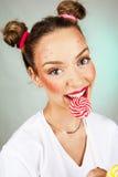 Bella ragazza felice con le lentiggini che tengono e che mangiano la lecca-lecca della caramella dei dolci con espressione faccia Fotografie Stock Libere da Diritti