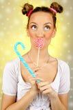 Bella ragazza felice con le lentiggini che tengono e che mangiano la lecca-lecca della caramella dei dolci con espressione faccia Immagini Stock Libere da Diritti