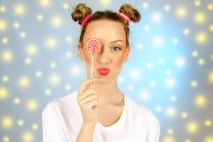 Bella ragazza felice con le lentiggini che tengono e che mangiano la lecca-lecca della caramella dei dolci con espressione faccia Immagini Stock