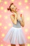 Bella ragazza felice con le lentiggini che tengono e che mangiano la lecca-lecca della caramella dei dolci con espressione faccia Fotografie Stock