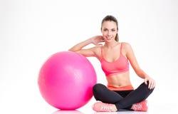 Bella ragazza felice di forma fisica che si siede e che posa con il fitball rosa Immagine Stock