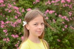 Bella ragazza in fiori rosa Fotografia Stock