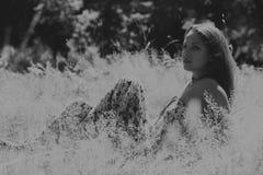 Bella ragazza fra i giacimenti di fiore fotografie stock
